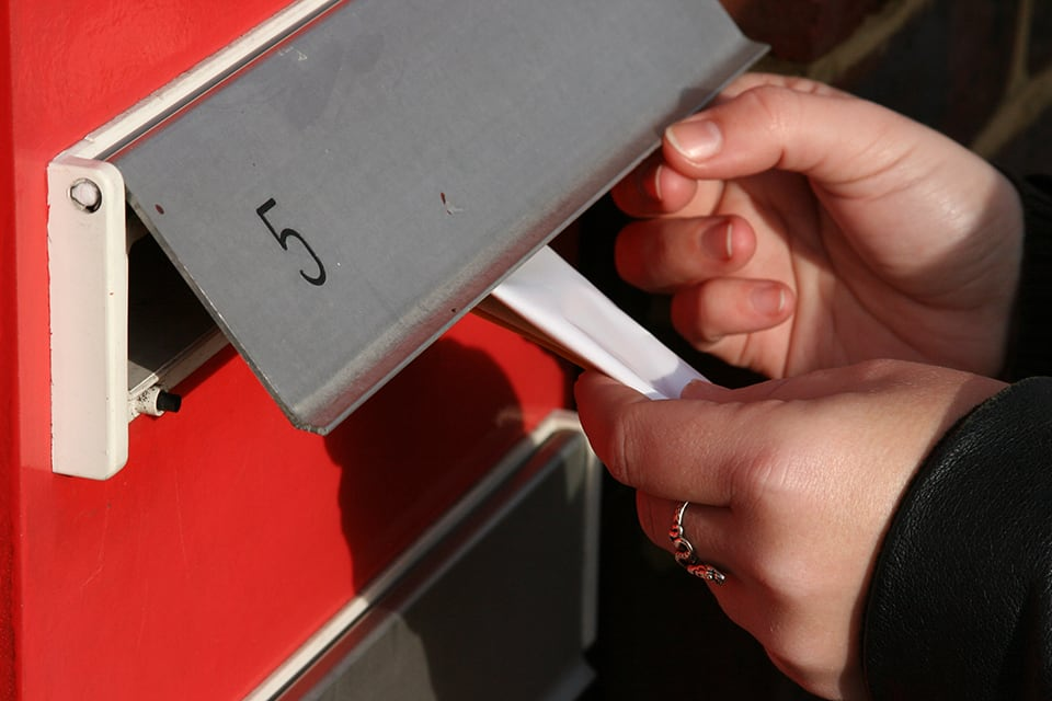 letterbox distribution with person putting mail in letterbox